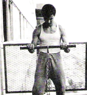 Bruce Lee working performing a bicep curl exercise